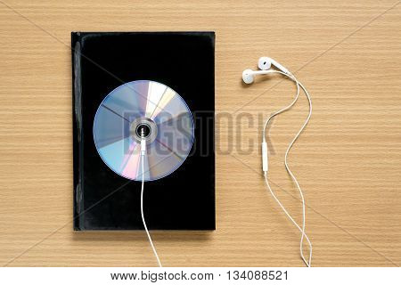 top view of notebook and dvd dish with earphone on wood background