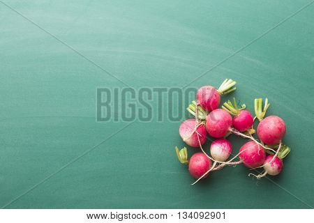 Fresh radishes on green chalkboard. Healthy vegetable. Top view of red radishes.