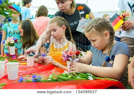 Zaporizhia/Ukraine- June 5, 2016: girls participating at floristic workshop, learning to make bouquets of fresh flowers, on charity family festival organized in regions with most quantity of refugees from Donetsk area, occasioned with International Childr