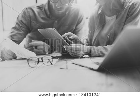 Coworking process. Photo young business crew working with new startup project.Notebook on wood table.Woman showing reports digital tablet, man holding document.Blurred background, black white.Horizontal