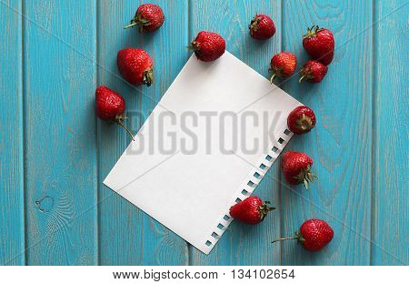 Strawberries on wooden grey and blue desk with white paper sheet. Stock photo.