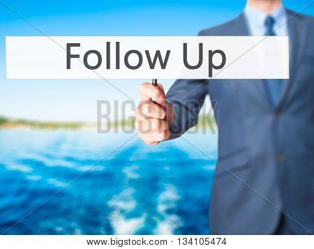 Follow Up - Businessman Hand Holding Sign