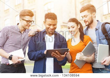 Cheerful four students are enjoying university life. Young man is holding a tablet. His friends are looking at it with interest and smiling. They are carrying laptops and book