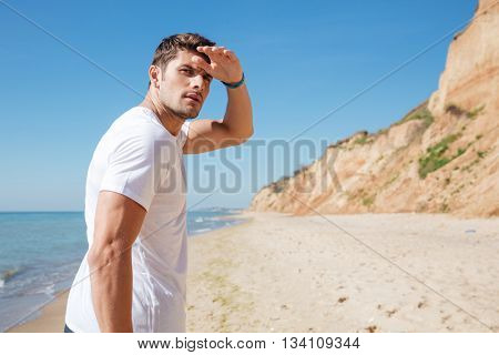 Concentrated attractive young man walking on the beach and looking far away