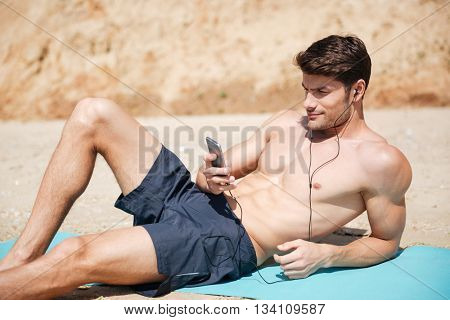 Attractive athletic young man lying and listening to music from mobile phone on the beach