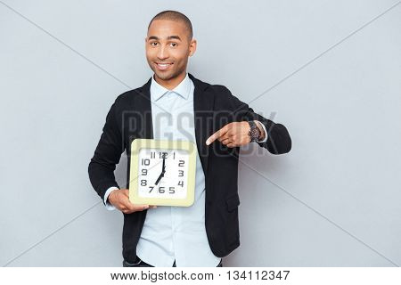 Happy african american young man holding clock anf pointing on it
