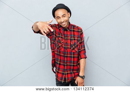 Cheerful attractive african man pointing on you