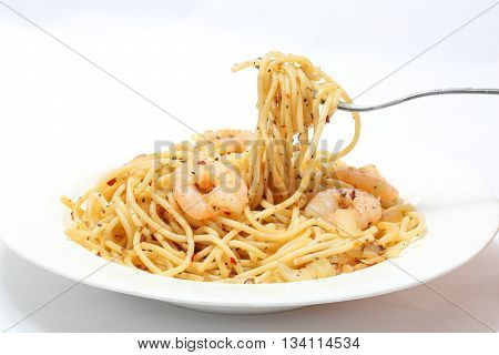 Seafood Spaghetti with prawn and herbs on plate fork shite background