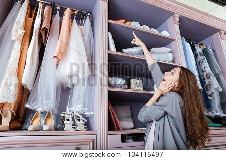 Young attractive woman choosing what to wear in a closet