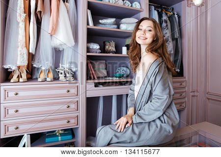 Beautiful young woman don't know what to wear sitting in her closet