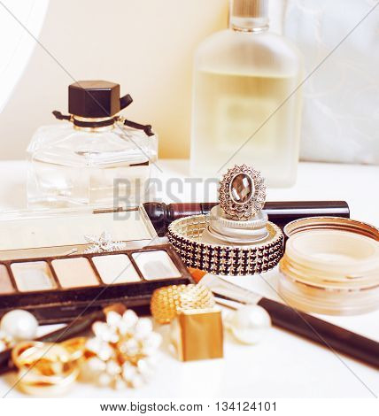 Jewelry table with lot of girl stuff on it, little mess in cosmetic brushes, real woman interior concept