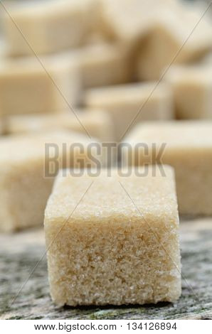 Many sugar brown cubes on wooden table