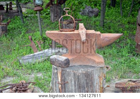 rusted old blacksmith anvil with a sledge hammer on a wooden stump