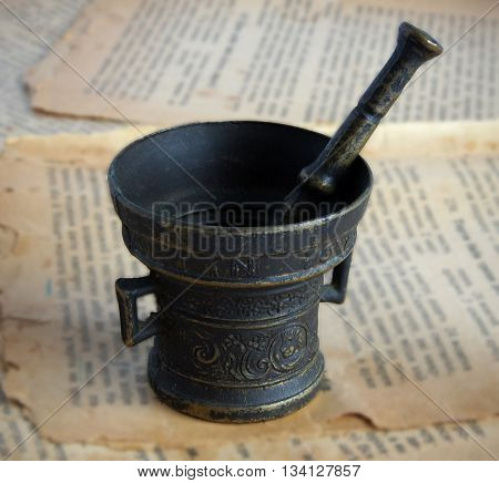 Old bronze mortar and pestle on the pages of ancient book with effect of shallow depth of field