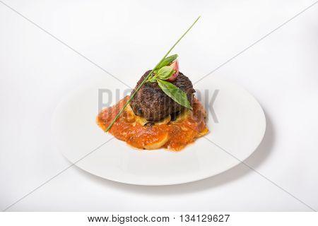 Prepared mignon steak with potato garnish and sauce