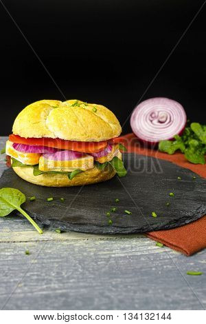 Healthy Vegetarian Veggie Sandwich with French soft cheese rocket ruccola salad red onion and paprika on black stone plate