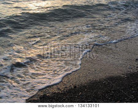 White foam glows between stony coast and water surface. Marina di Cecina Livorno Italy poster
