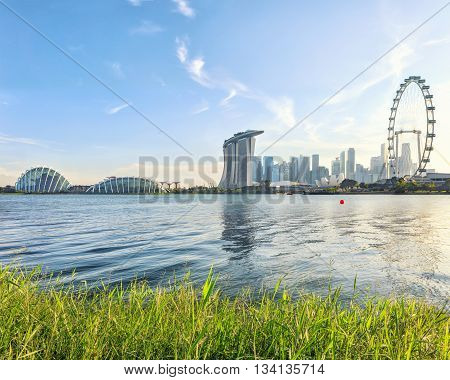 Singapore Marina Bay from Marina East with grass on foreground. Modern city architecture at sunset