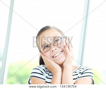 Cute girl is holding her face in astonishment and looking up