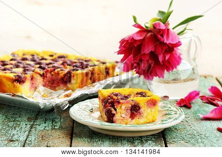 Homemade quark pie with cherries and red peony falling petals on old wooden background horizontal