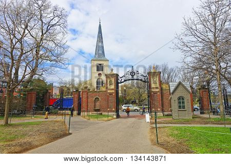 Cambridge, USA - April 29^2015: First Parish Church in Cambridge in Harvard Square and tourists at Harvard Yard in the campus of Harvard University in Cambridge Massachusetts MA USA. The church is built 400 years ago.