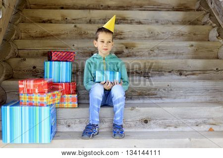 many gifts in birthday. boy in a festive cap sitting on the stairs with lots of gifts. copy space for your text