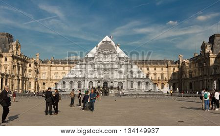 Paris France-June 09 2016 : The Louvre pyramid covered by french street artist JR with colossal black and white photos of the 16th century buildings surrounding the monument making it appear as if it not there at all.