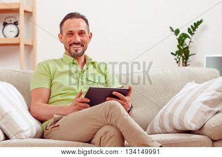 Portrait of handsome businessman using tablet PC at home. Happy man sitting on safa or couch and working from home.