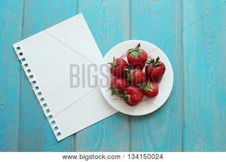 Strawberries in white plate on wooden blue desk. Stock photo.