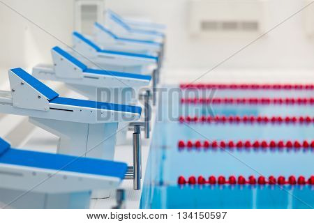 Starting blocks and lanes in a swimming pool.