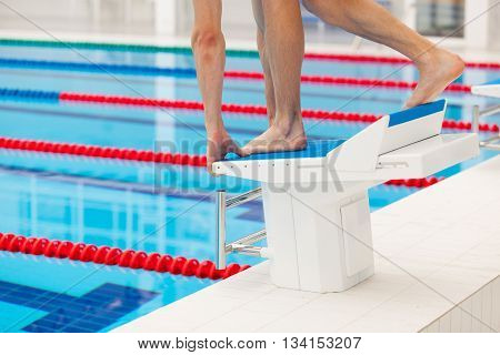 Young muscular swimmer in low position on starting block in a swimming pool.