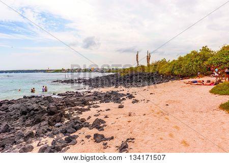 Puerto Ayora Santa Cruz Ecuador - April 11 2016: People at the beach called Playa de la Estacion. This is a nice little beach not far from the entrance to the Charles Darwin research center in Santa Cruz island in Galapagos