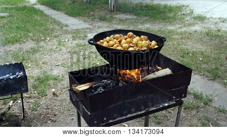 Potatoes cooked in a cast iron cauldron on the grill at a picnic