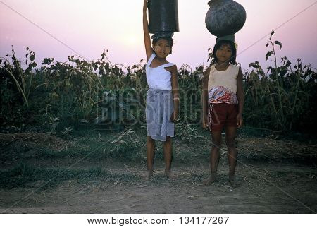 MYANMAR BURMA - CIRCA 1987: Two young girls carry jugs on their heads against a sunset.