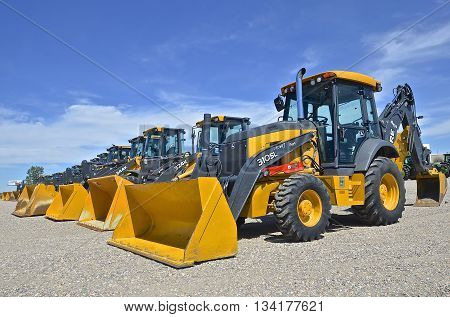 MOORHEAD, MINNESOTA, June 6, 2016: The row of backhoe excavators and front end loaders are products of John Deere Co, an American corporation that manufactures agricultural, construction, forestry machinery, diesel engines, and drivetrains.
