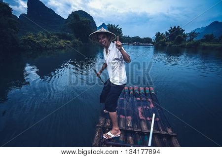 Guilin China - June 18 2014 : A shot of a local chinese wearing a traditional hat paddling a bamboo raft during a river cruise in Guilin China.
