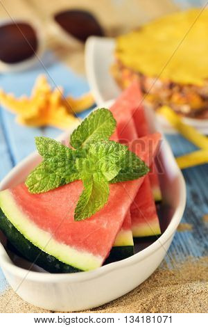 closeup of a bowl with some slices of watermelon on a blue rustic wooden surface next to some yellow starfishes, a plate with some slices of pineapple and a pair of sunglasses in the background