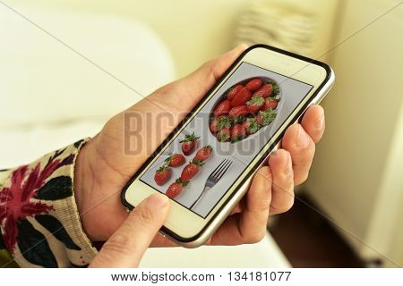 closeup of a young caucasian man with his smartphone ins his hands, with a picture of a bowl with strawberries, taken by myself, in its screen