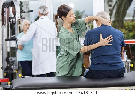 Physiotherapist Massaging Senior Man's Back