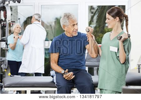 Nurse Instructing Senior Male Patient Exercising With Dumbbell