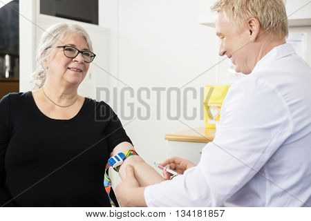 Smiling Patient Looking At Male Doctor Collecting Blood In Syrin