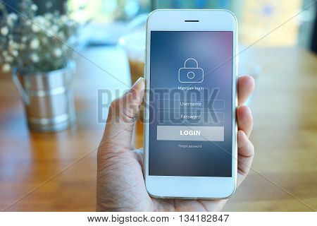 Hand holding smartphone with receive newsletter form screen on cafe background
