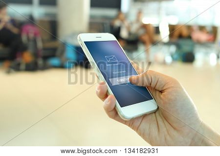 Hand holding smartphone with member loging screen on airport background poster