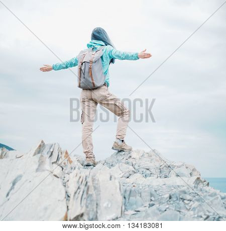 Happy traveler young woman standing with raised arms on peak of cliff and enjoying a beautiful nature