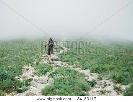 Hiker young man with backpack and trekking poles climbing up mountain in mist in summer outdoor rear view