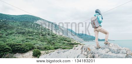 Unrecognizable traveler young woman with backpack standing on cliff coast and enjoying view of sea