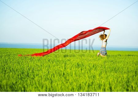 Young lady runing with tissue in green field. Beautiful happy woman walking in the summer rural meadow. Beautiful fit tan girl. Sexy slim model caucasian ethnicity outdoors.