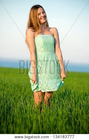 Happy playfull vitality freedom girl stands in green field. Woman lifestyle