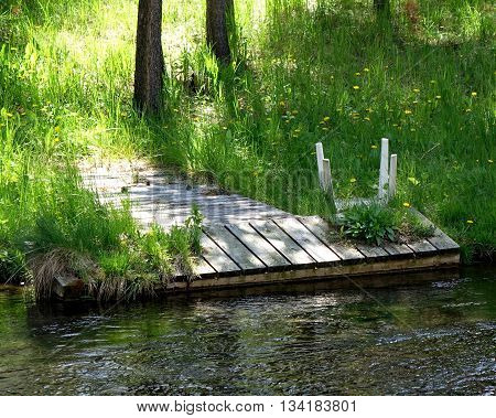 A personal small dock at the end of a pathway to the Deschutes River in Central Oregon.