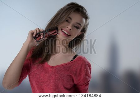 Happy casual young woman holding her glasses